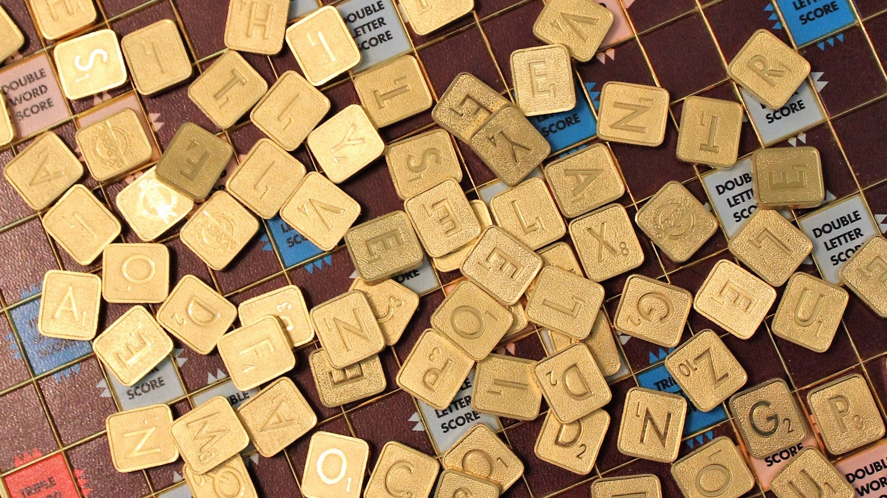 gold-plated Scrabble tiles scattered across the board