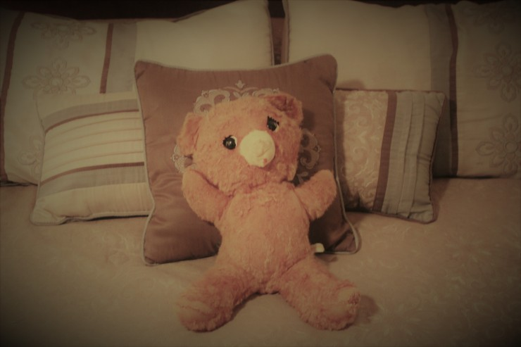 very old teddy bear leaning against bed pillows